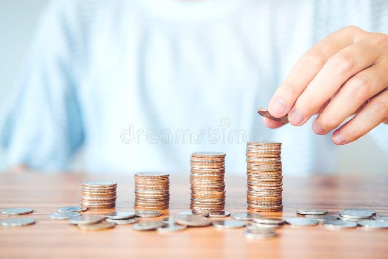 Main d'homme de concept d'argent d'économie mettant des finances de pile de pièce de monnaie pour le bourgeon photographie stock libre de droits