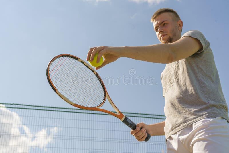 Main d'homme de joueur de tennis faisant un tir tenant une boule et une raquette contre le ciel photographie stock libre de droits