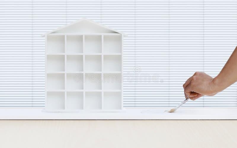 Main d'homme de peintre avec le modèle blanc de peinture de maison de pinceau dessus photos libres de droits