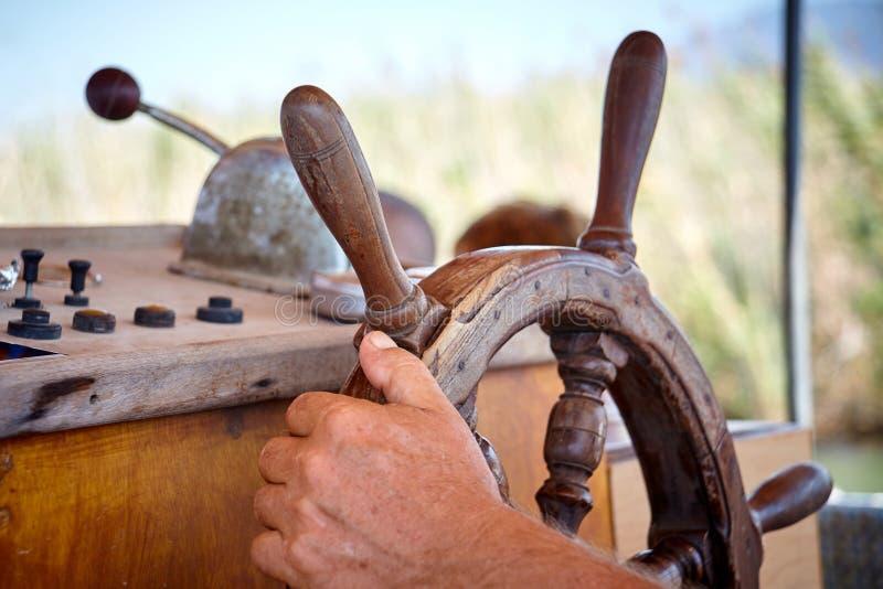 Main d'homme de plan rapproché tenant une roue de navire de navigation images libres de droits