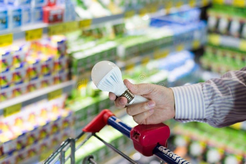 Main d'homme ou de femme tenant la lampe de rendement optimum d'ampoule de diodes avec le chariot sur le supermarché, magasin de  images stock