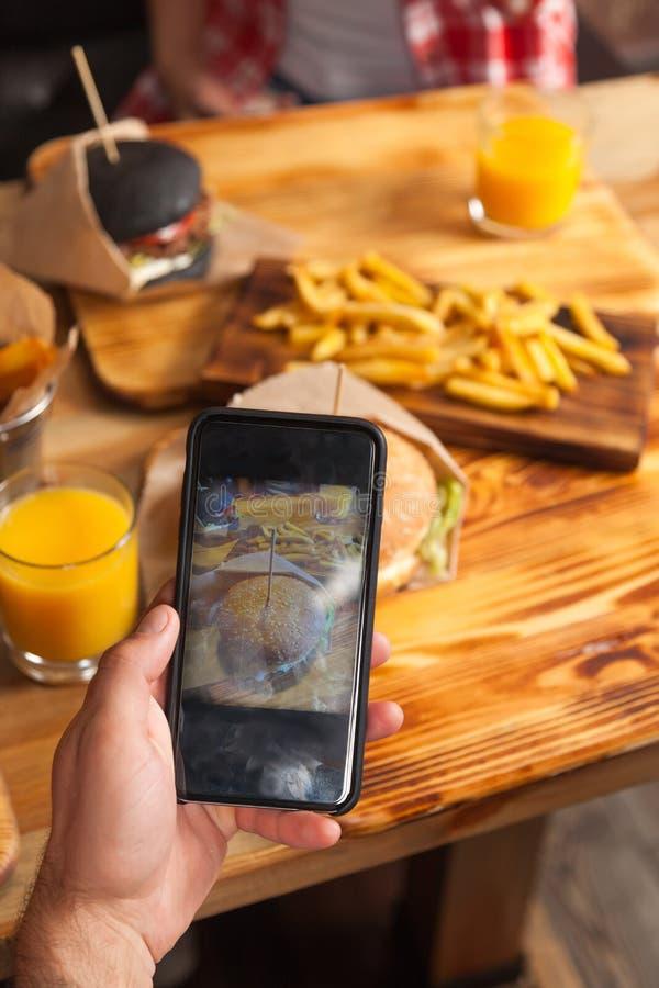 Main d'homme prenant la photo de l'hamburger Fried Potato Fast Food Served de boeuf en café en bois de papier de Tableau photos stock
