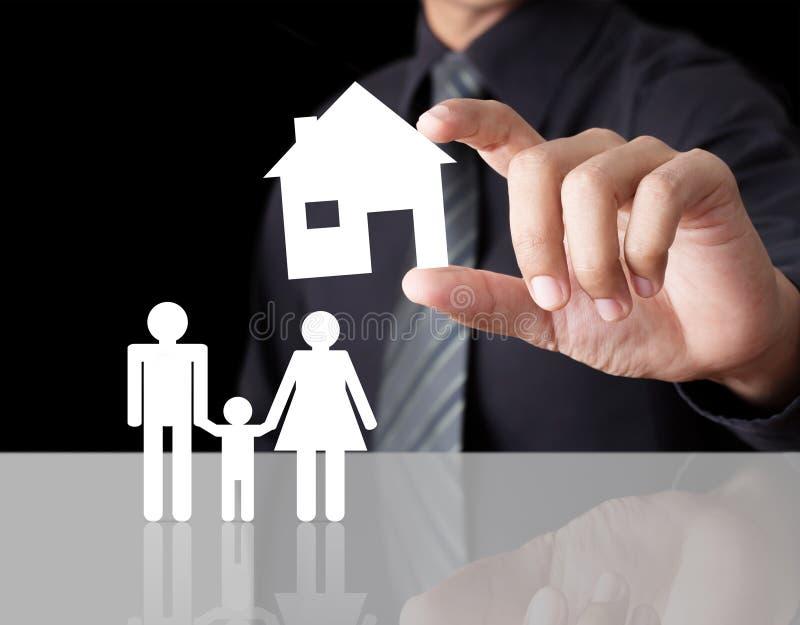 Main d'homme tenant la maison de papier avec la famille photo libre de droits