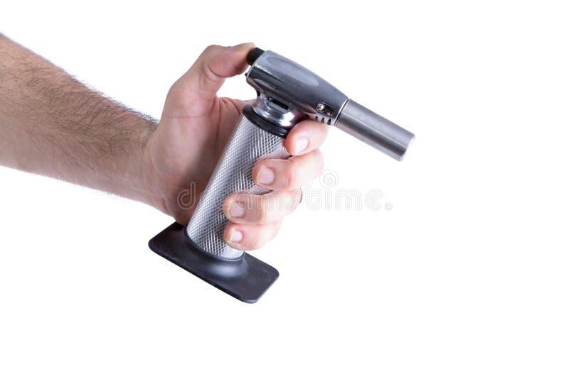 Main d'homme tenant la torche de cuisine de butane photographie stock libre de droits