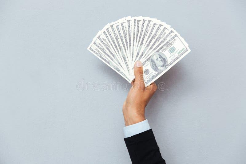 Main d'homme tenant les dollars américains images stock