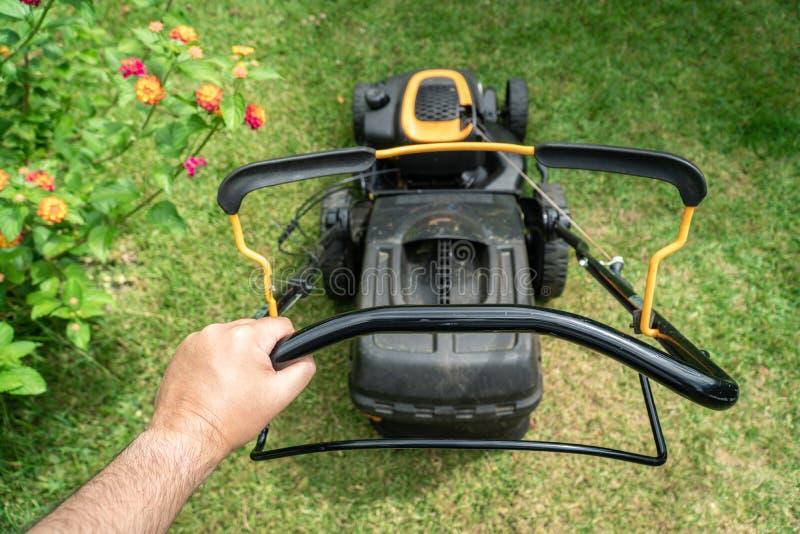 Main d'homme tenant une machine de tondeuse à gazon sur couper l'herbe verte photo libre de droits