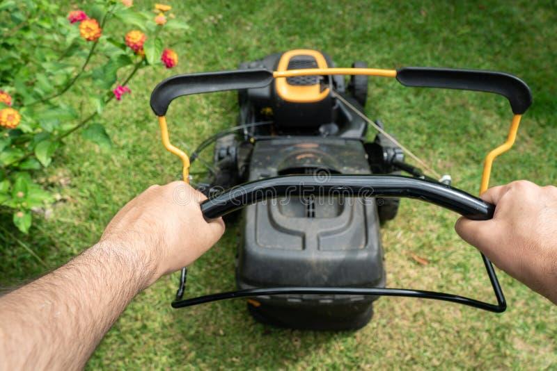 Main d'homme tenant une machine de tondeuse à gazon sur couper l'herbe verte image libre de droits