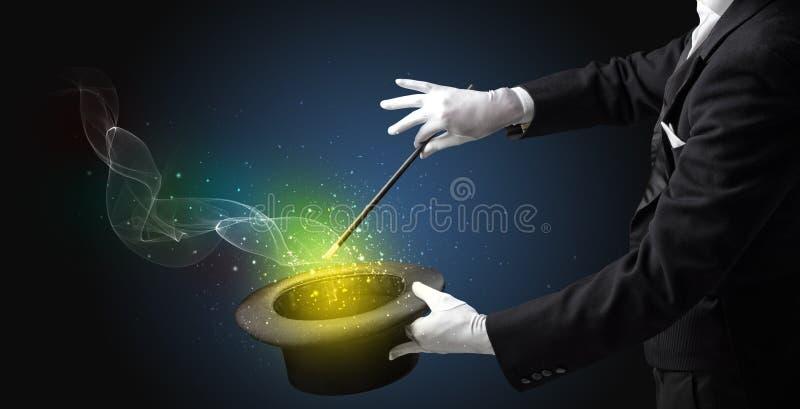 Main d'illusionniste faisant le tour avec la baguette magique photo stock