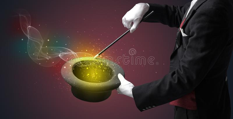 Main d'illusionniste faisant le tour avec la baguette magique images stock