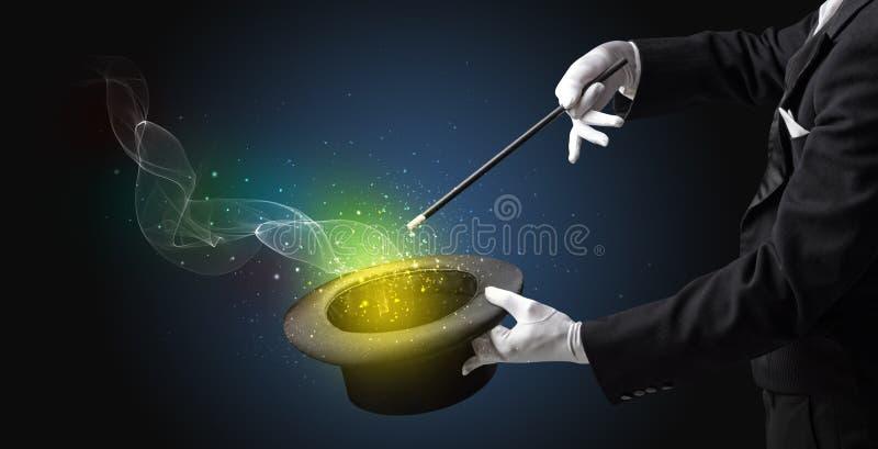 Main d'illusionniste faisant le tour avec la baguette magique image stock
