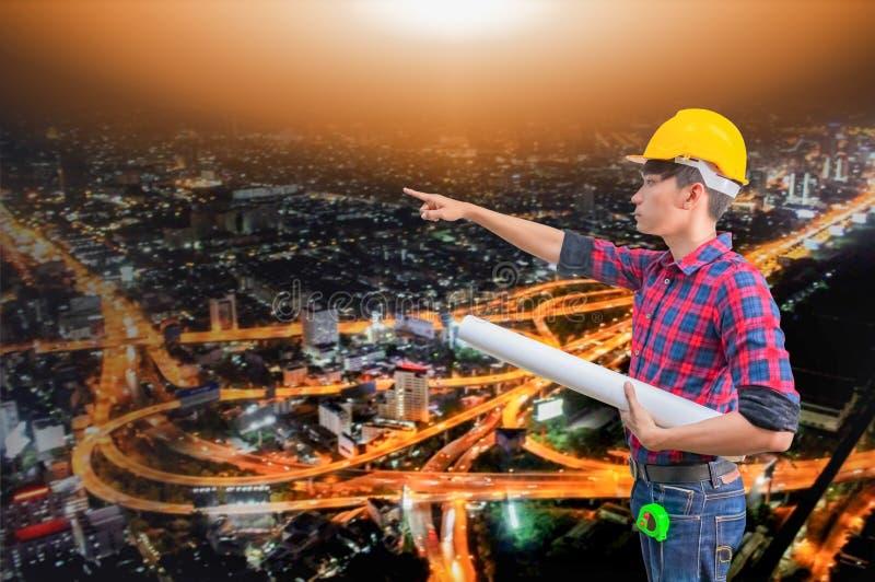 Main d'ingénieur dirigeant et tenant les modèles roulés dans le concept de construction avec le fond brouillé par ville de nuit photo libre de droits