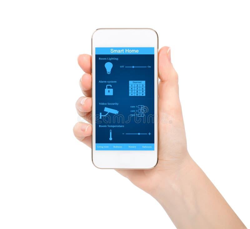 Main d'isolement de femme tenant le téléphone avec la maison futée de système photo stock