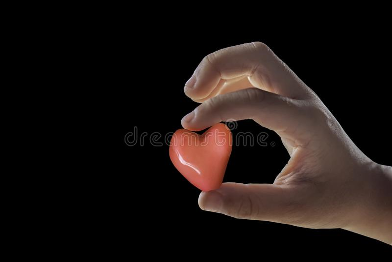 Main d'isolement tenant un coeur rouge de forme de sucrerie sur un backgro noir photos libres de droits