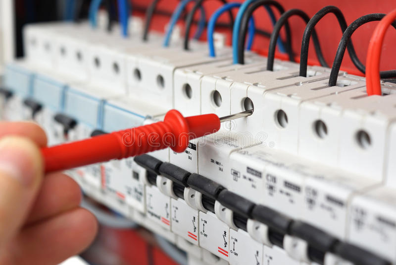 Main d'un électricien avec la sonde de multimètre sur un commutateur électrique photos libres de droits