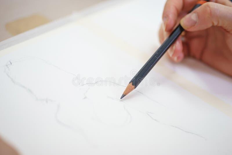 Main d'un artiste avec un plan rapproché de crayon tout en dessinant un croquis sur le papier propre photo libre de droits