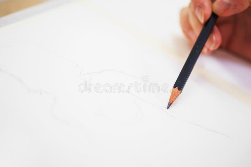Main d'un artiste avec un plan rapproché de crayon tout en dessinant un croquis sur le papier propre photos libres de droits