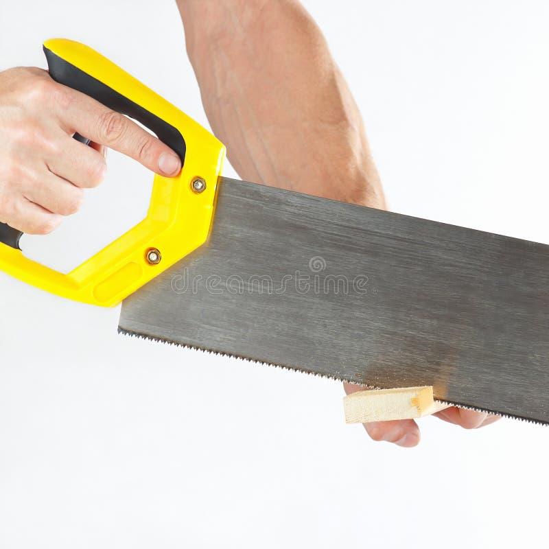 Main d'un charpentier coupant un bloc en bois avec une scie à main images stock