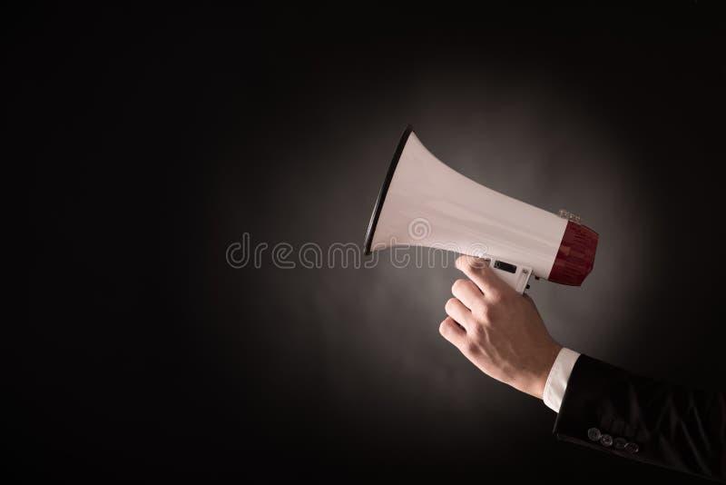 Main d'un homme d'affaires tenant un mégaphone photos stock