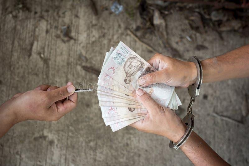 Main d'un homme dans des menottes donnant le paiement illicite, image stock