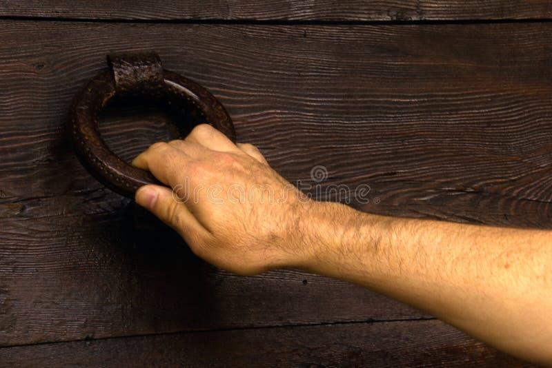 Main d'un homme frappant à la porte image stock