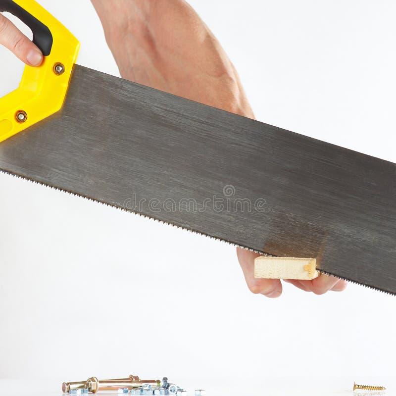 Main d'un menuisier coupant le bloc en bois avec la scie à main photo libre de droits