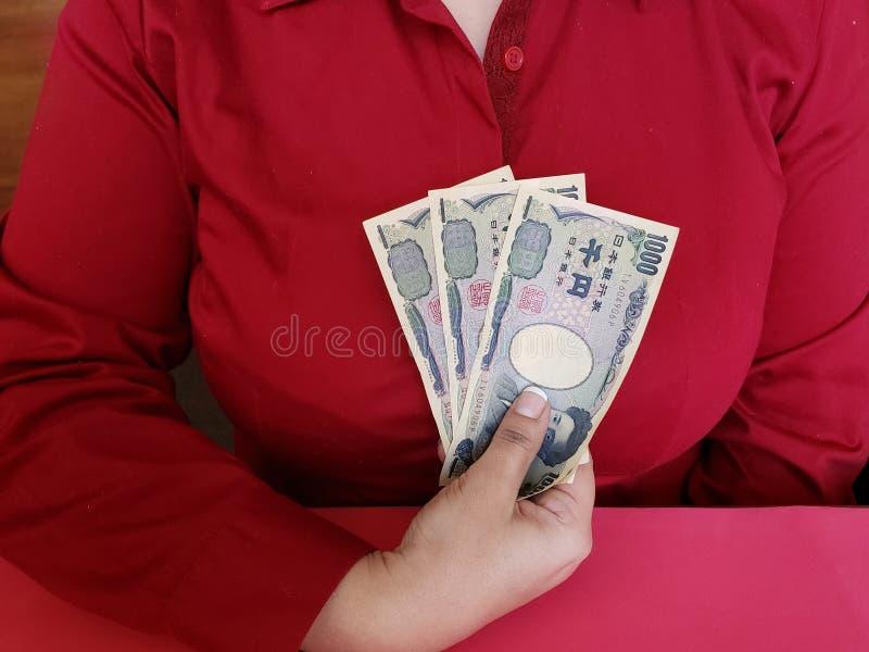 main d'une femme d'affaires tenant les billets de banque japonais photos libres de droits