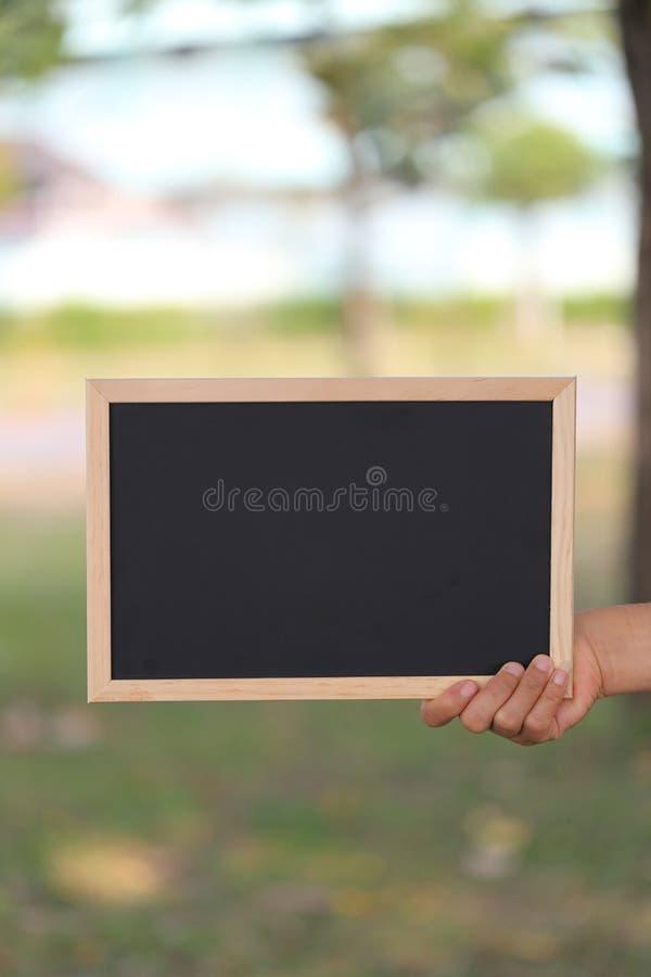 Main d'une femme d'affaires tenant une photo en bois noire vide franc photos libres de droits