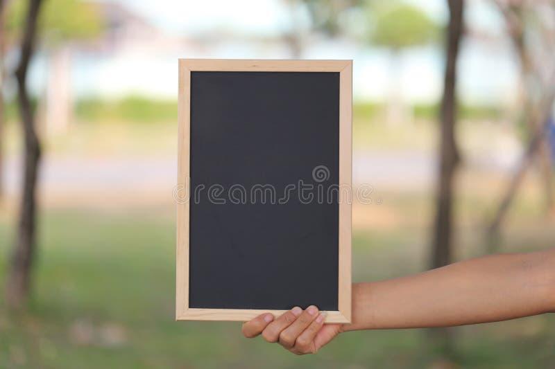 Main d'une femme d'affaires tenant une photo en bois noire vide franc photographie stock libre de droits