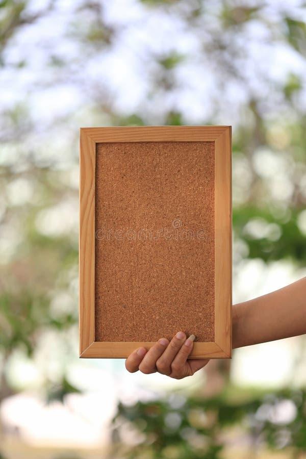 Main d'une femme d'affaires tenant un cadre de tableau en bois vide dessus photos libres de droits