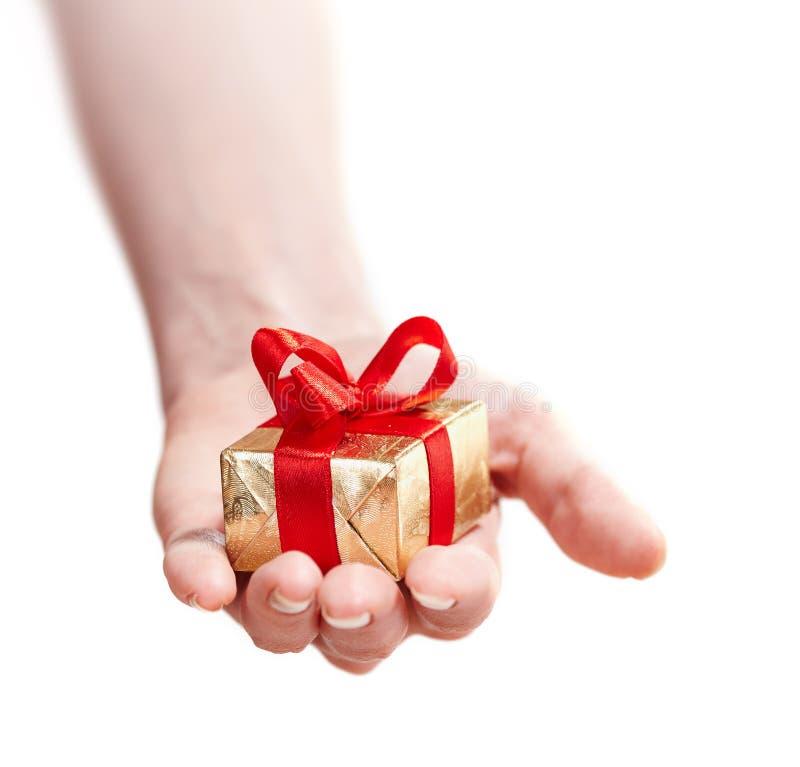 Main d'une fille avec un cadeau d'isolement sur le blanc image libre de droits