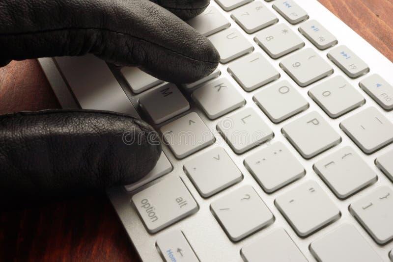 Main dans des types de gant sur le clavier image stock