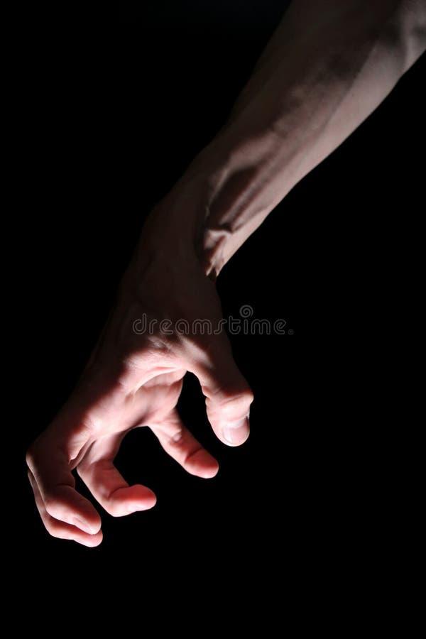 Main dans l'obscurité photo stock