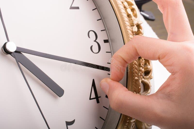 Main dans le contact avec une horloge photo stock