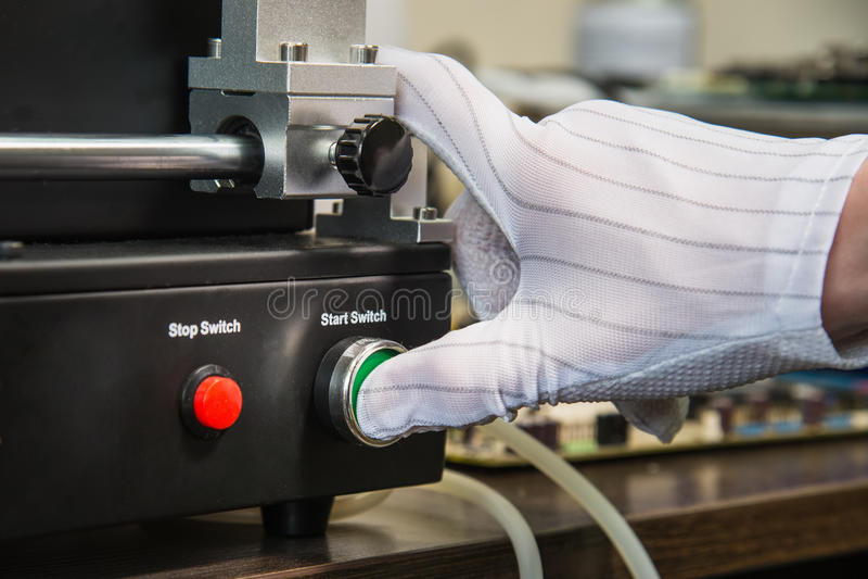 Main dans le gant antistatique blanc pressant le bouton marche vert sur la boîte électrique photos libres de droits