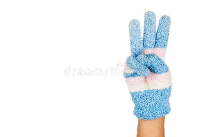 Main dans le geste bleu de gant d'hiver numéro trois contre le CCB blanc photo libre de droits
