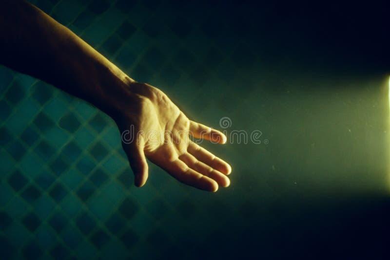 Main dans le rayon de la lumière sous l'eau image stock