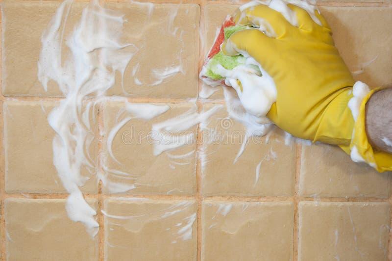 Main dans les gants jaunes avec l'éponge lavant la tuile Concept de nettoyage image libre de droits