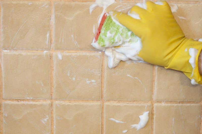 Main dans les gants jaunes avec l'éponge lavant la tuile Concept de nettoyage photographie stock libre de droits