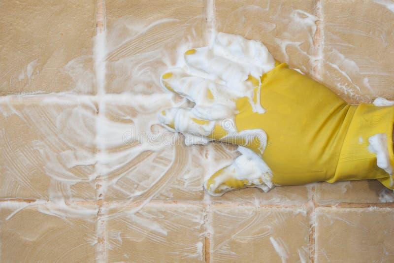 Main dans les gants jaunes avec l'éponge lavant la tuile Concept de nettoyage image stock