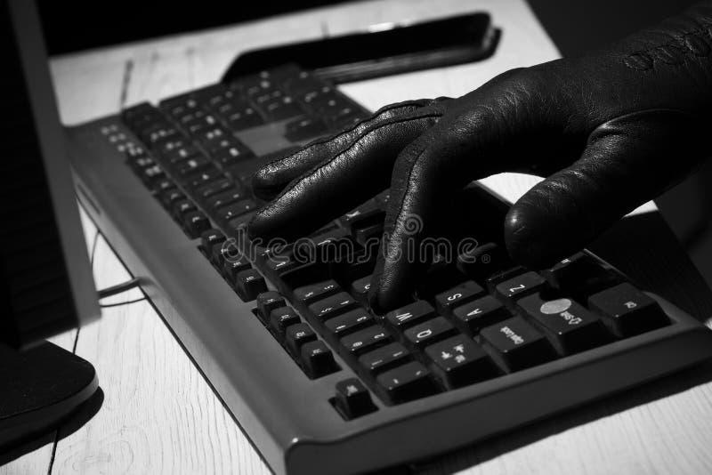 Main dans les types noirs de gant sur le clavier photographie stock libre de droits