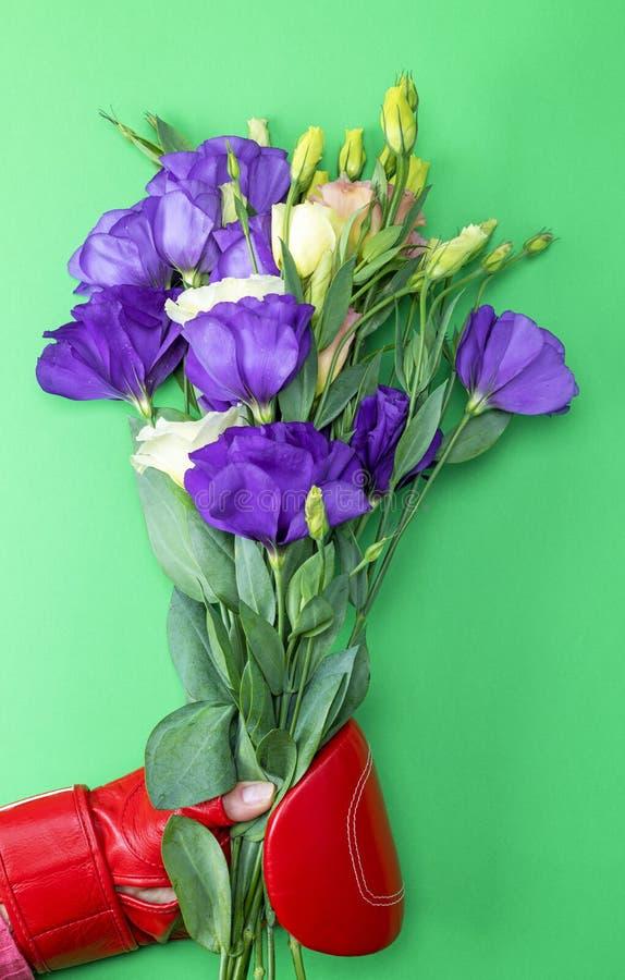 Main dans un gant de boxe rouge tenant un bouquet des fleurs photo stock
