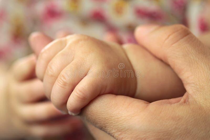 Main de bébé dans la main de père, macro tir images stock