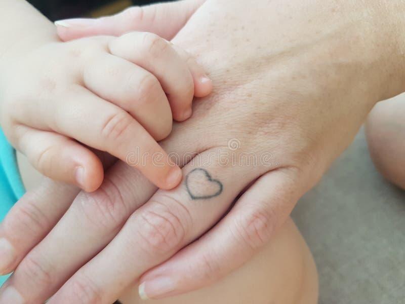 Main de bébé garçon avec la main de la maman photos stock