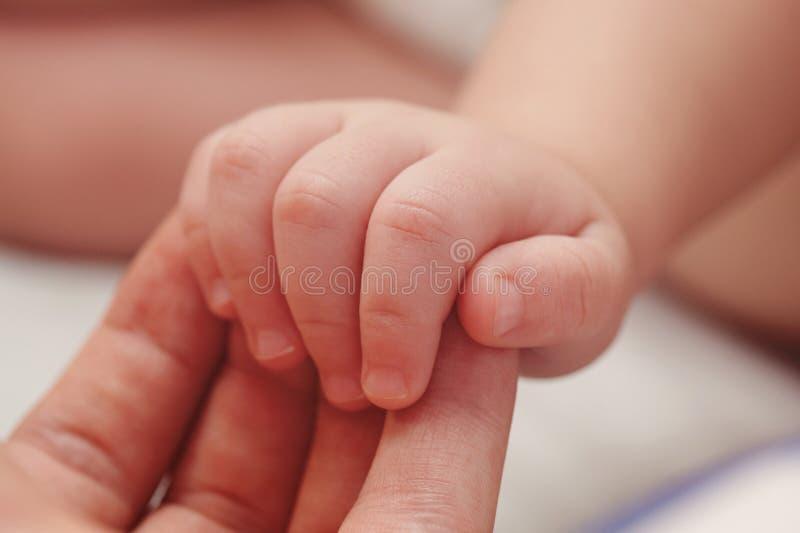 Main de bébé sur la paume de parent images stock