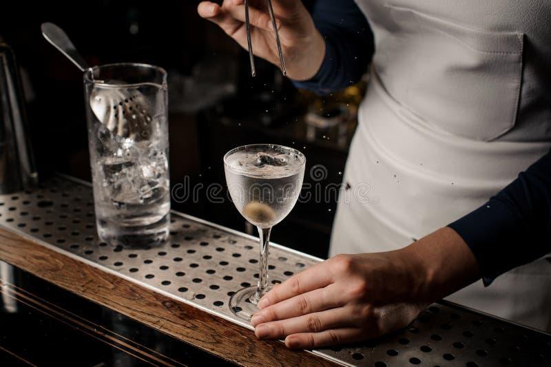 Main de barmaid mettant une olive dans un verre de cocktail image stock