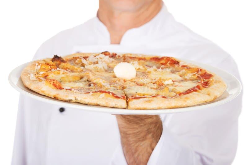 Main de boulanger de chef avec la pizza italienne image stock