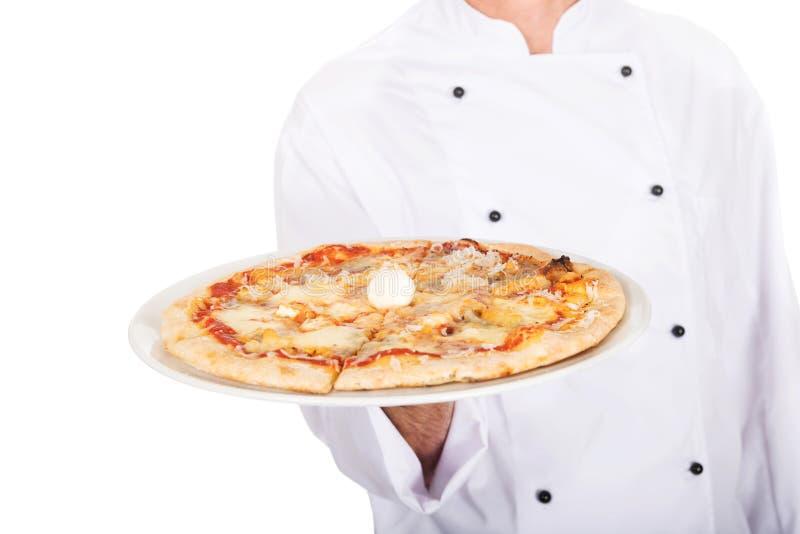 Main de boulanger de chef avec la pizza italienne du plat photographie stock libre de droits