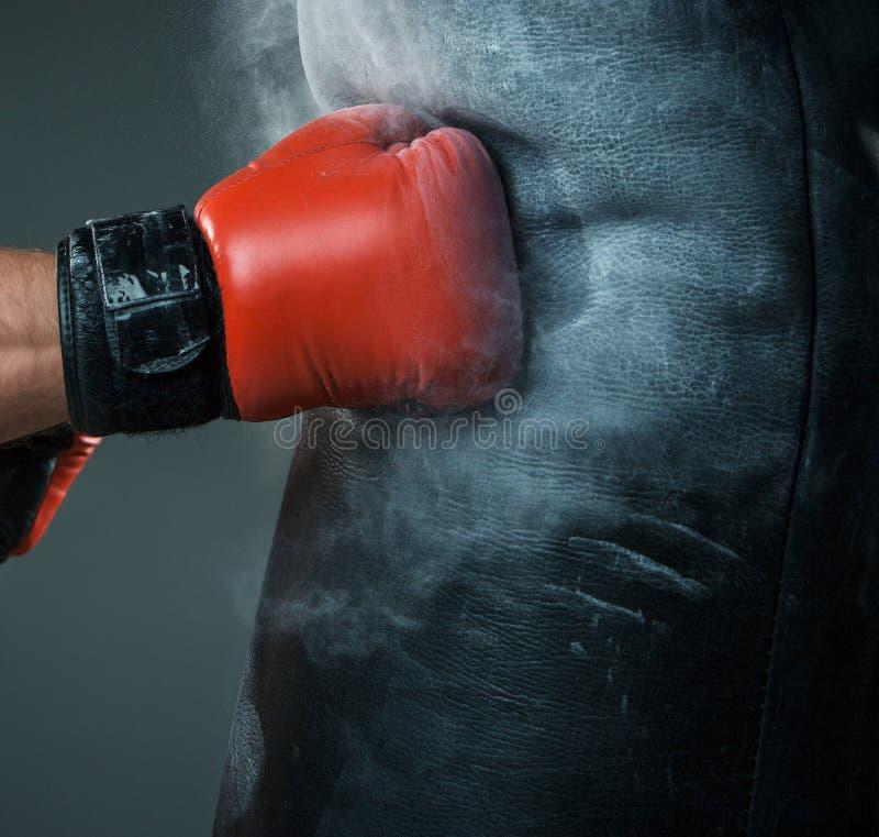 Main de boxeur et de sac de sable au-dessus de noir photographie stock libre de droits