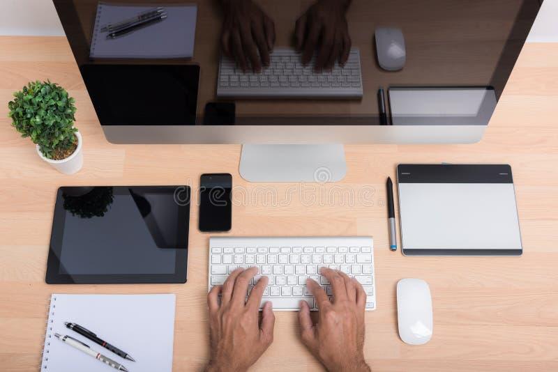 Main de bureau de vue supérieure travaillant sur le PC d'ordinateur images libres de droits