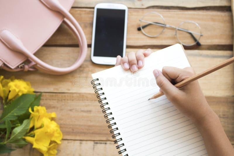 Main de carnet d'écriture d'étudiante pour l'étude photo libre de droits